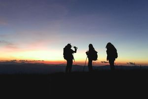 People in backpacks standing together with the sun setting behind them