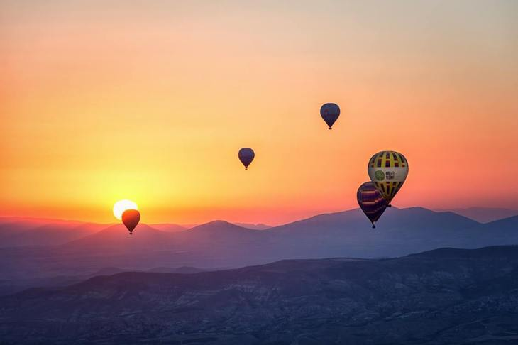 Assorted hot air balloons in the sky during sunset