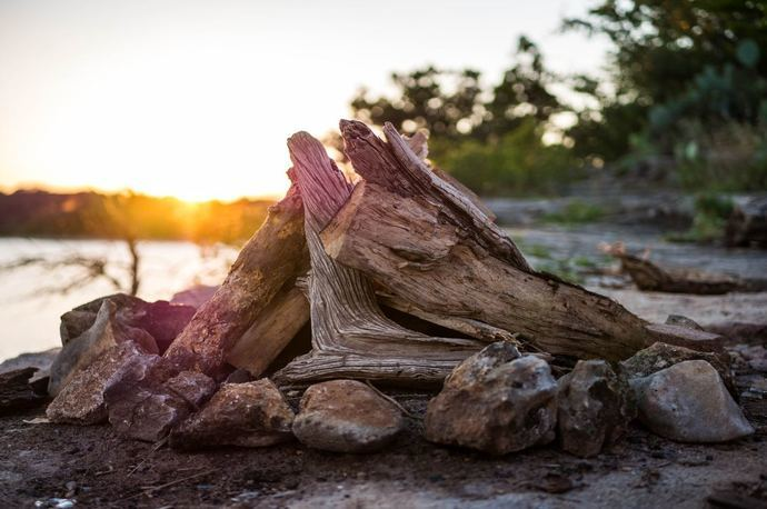 Woods stacked in a teepee on top of a bed of rocks on the beach