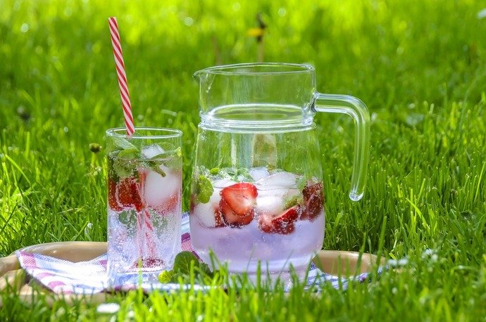 Water with strawberries and mint leaves sitting on the grass
