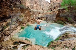 A man jumping off a cliff into a pool of turquoise water
