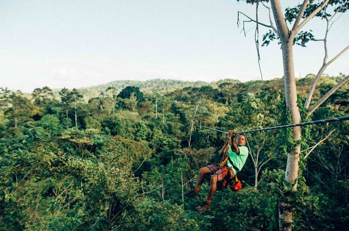 A man hanging on a zip line high in jungle trees