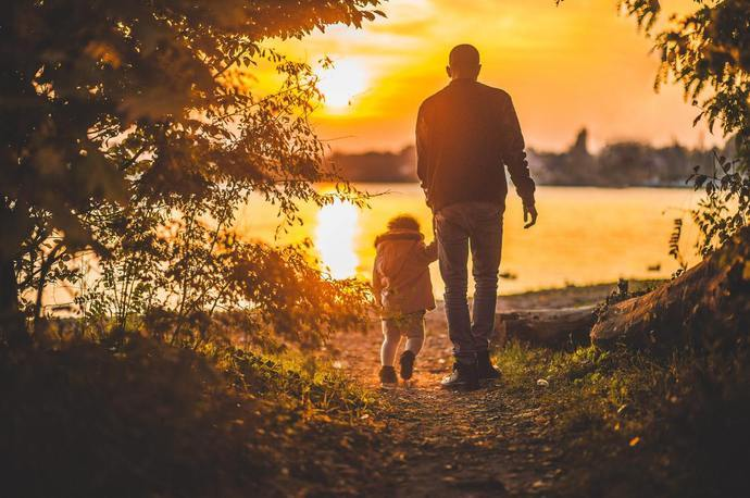 A man walking with a young child outdoors at sunset