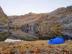 A bivy sack set up next to an alpine lake