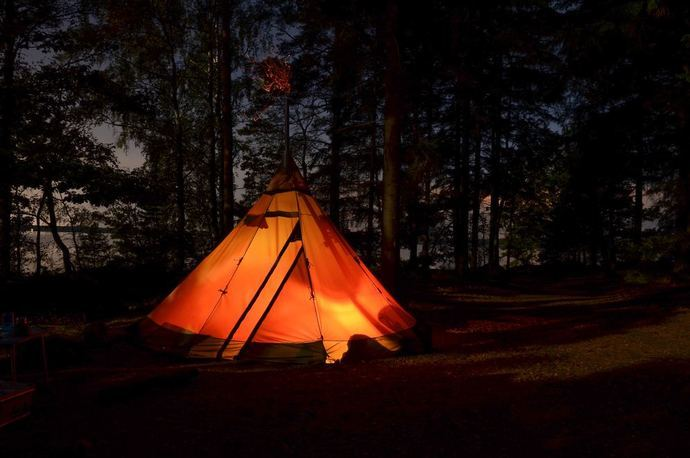 A tent shapes like a teepee glowing in the night