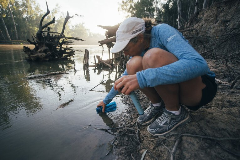 Person drinking water out of a personal straw filter.