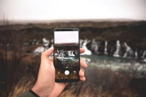 Person holding a phone with a waterfall in the background