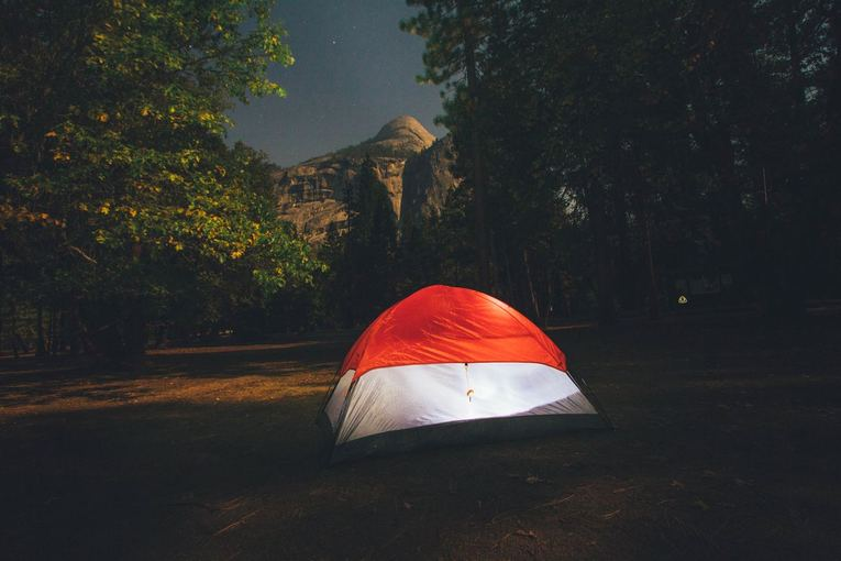 red and white camping tent surround by trees during nighttime