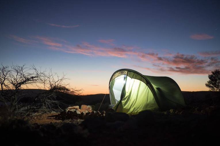 Tent illuminated at dusk in the desert.