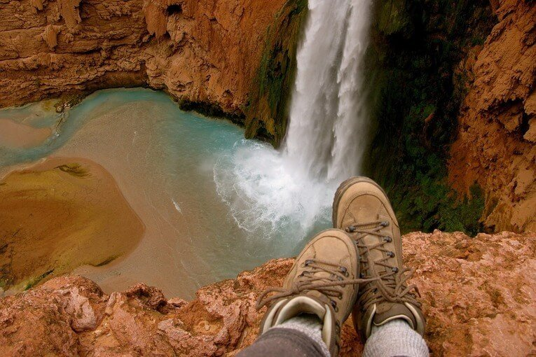 Person in boots overlooking a waterfall