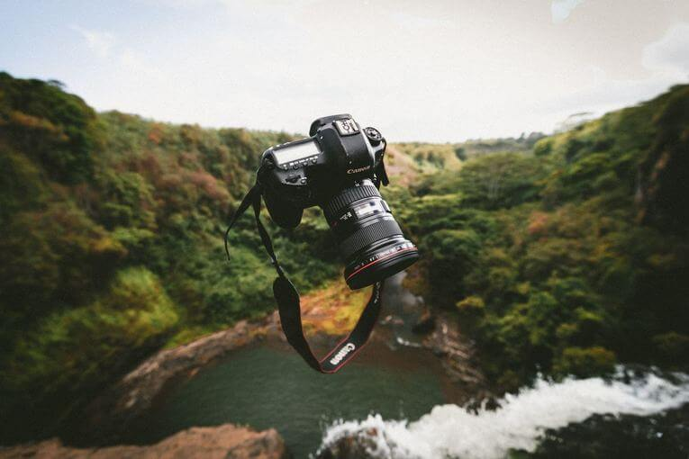 A camera being tossed in the air outdoors.