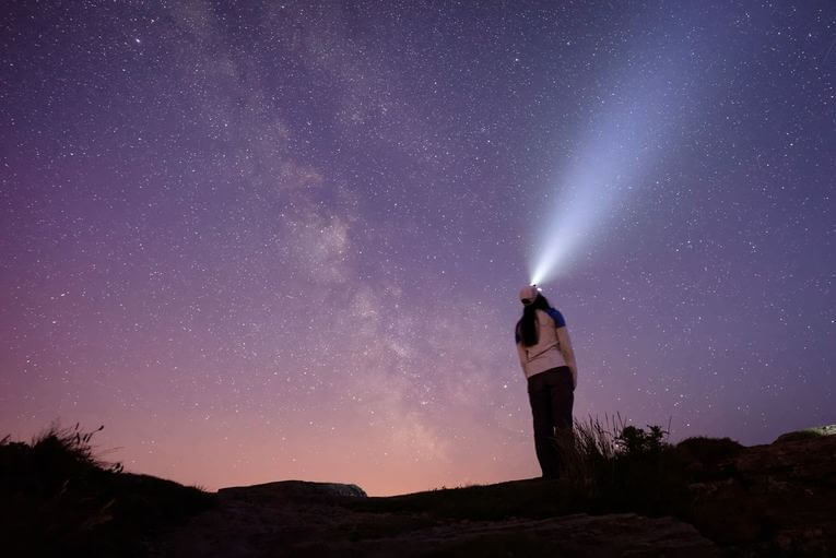 A person looking up into the sky with a headlamp on,