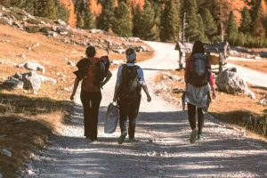 Three women walking with backpacking on a hiking trail.