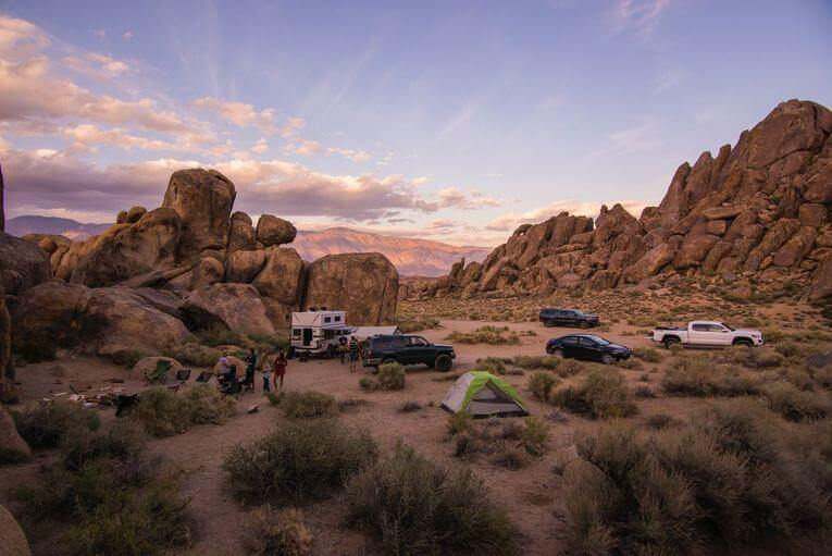 A group of cars and tents in the desert.
