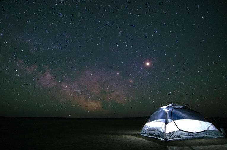 A tent lit up at night under the stars.