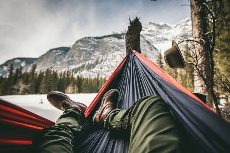 Person laying in a hammock outdoors.