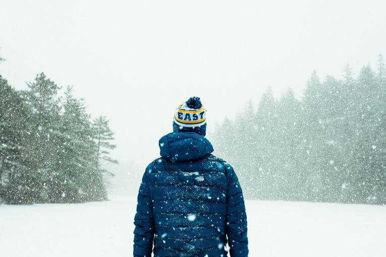 Person standing in the snow with a jacket and beanie on.