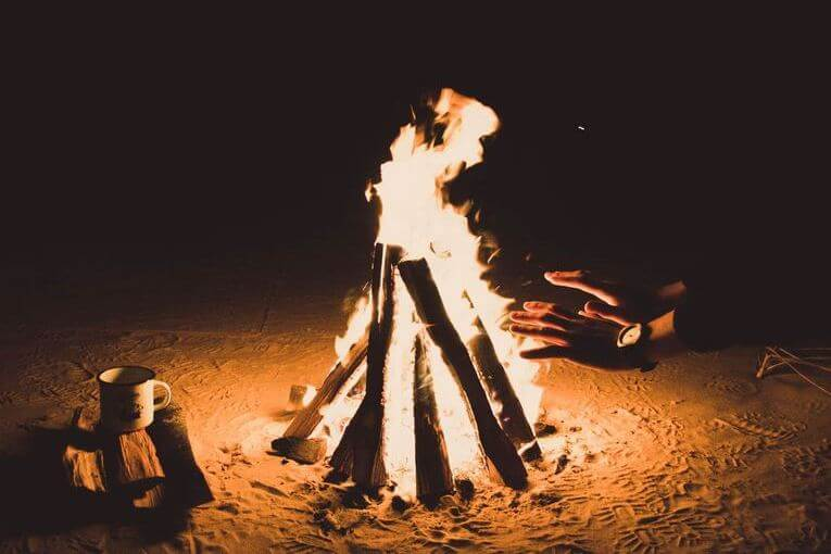 A person warming their hands around a bonfire.