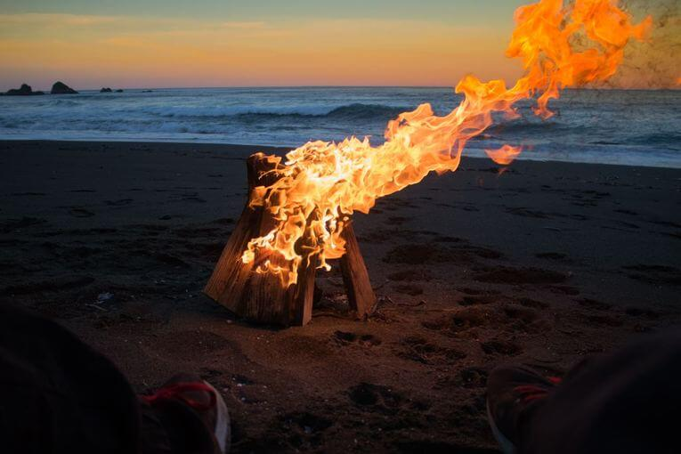 Logs burning on the beach at sunset.