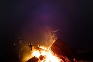 Logs burning at night underneath a starry sky