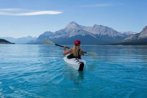 A woman wearing red hat riding on white kayak facing mountain alps