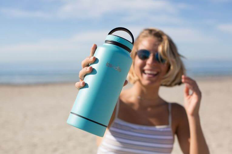 Women holding blue water bottle on the beach