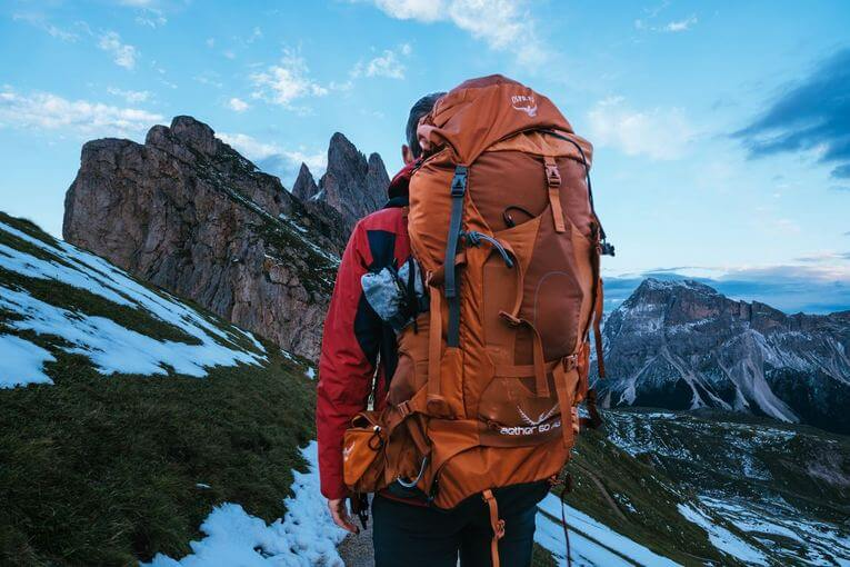 Person standing in the mountains with a large orange osprey backpack