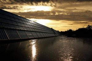 Black solar panel near calm body of water at sunset