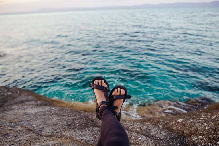 person sitting in sandals by the water