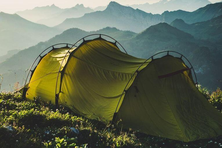 Green tent sitting on a mountaintop