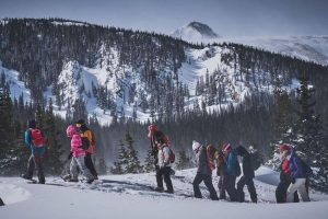 People walking on icy mountain in snowshoes