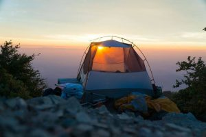A tent sitting on a cliff at sunset