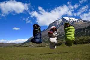3 women jumping in the air wrapping in sleeping bags