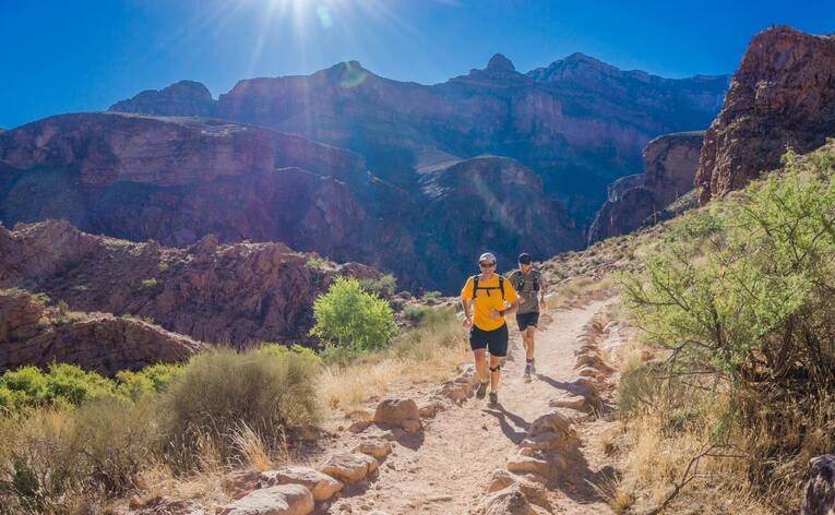 2 people running on a trail in the mountains